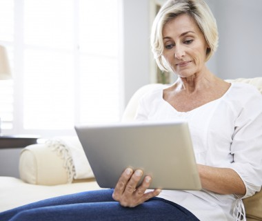 Shot of a senior woman using a digital tablet while sitting on the sofa at home